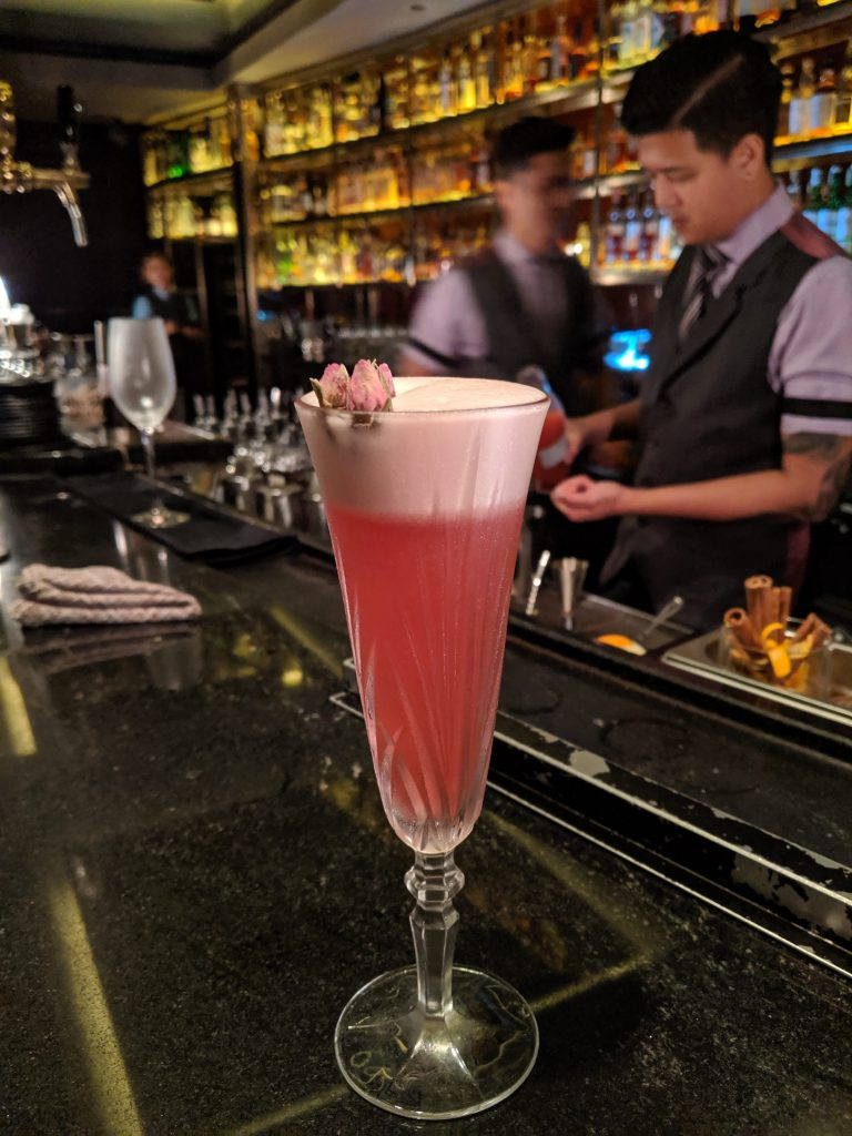 cocktail bars in singapore manhattan with bartenders moving behind the drink