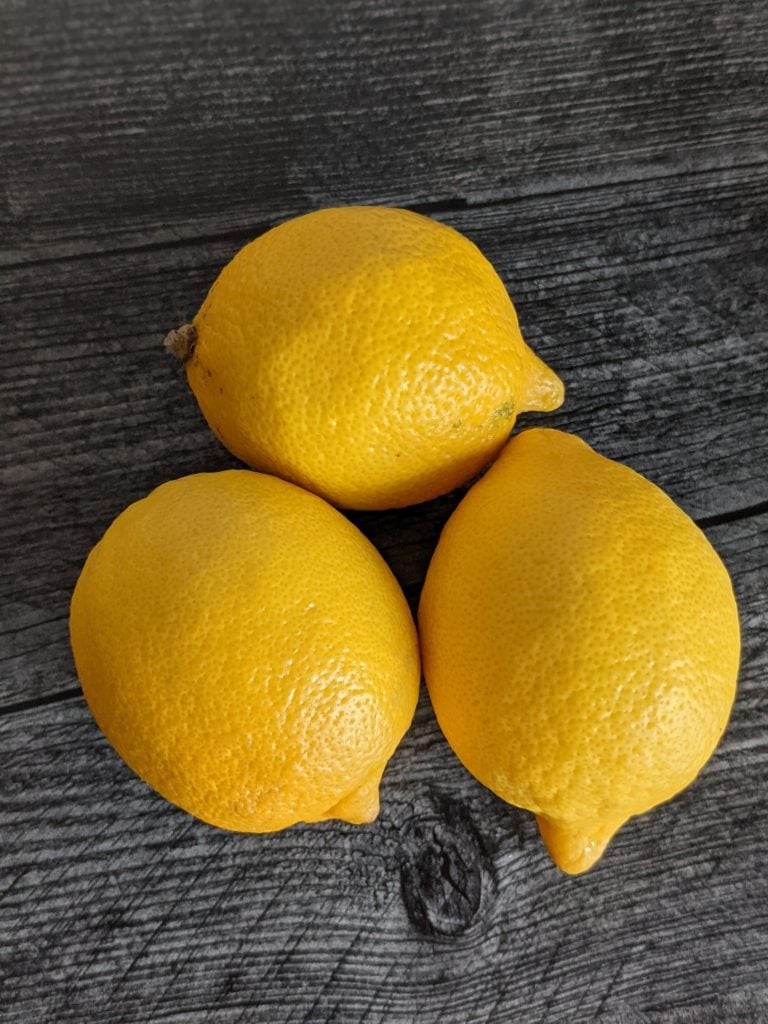 three fresh lemons for making lemonade in a blue lagoon cocktail