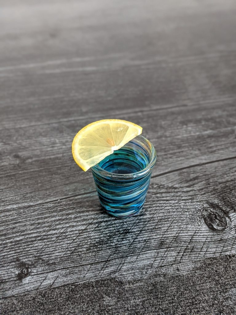 blue lagoon cocktails as a cocktail shooter on fire in a handblown shot glass