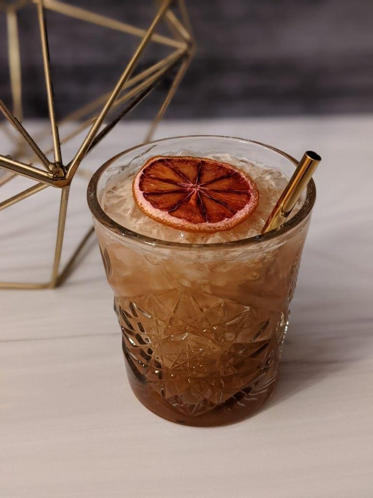 zirbenz cocktail with blood orange garnish and tiki vibes