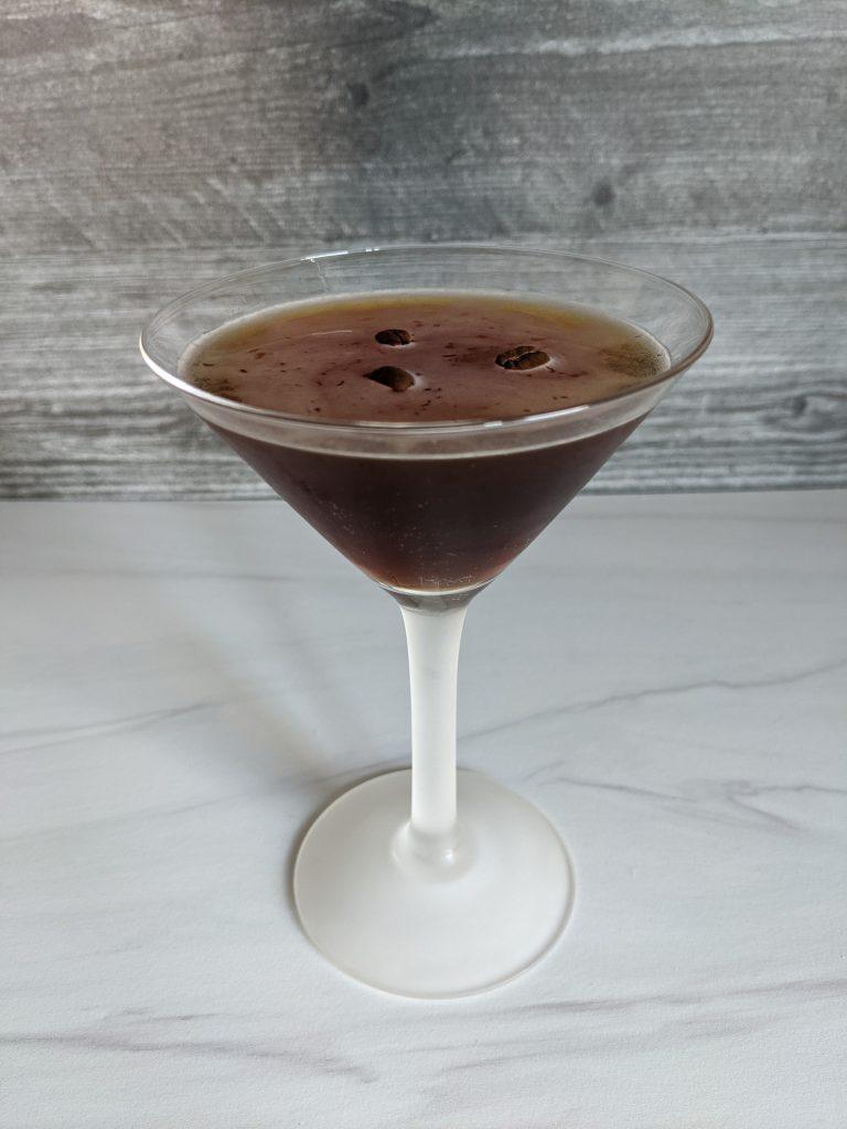 classic espresso martini in a martini glass with three coffee beans